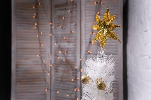 Biała choinka ze złotymi i srebrnymi bombkami świątecznymi dekoracjami