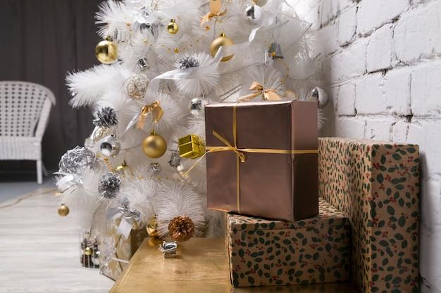 Biała choinka ze złotymi i srebrnymi kulkami pudełka na prezenty świąteczne dekoracje