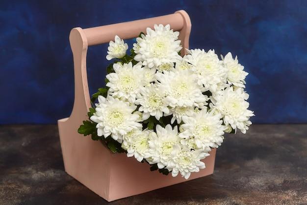 Biała chryzantema kwitnie w drewnianym pudełku