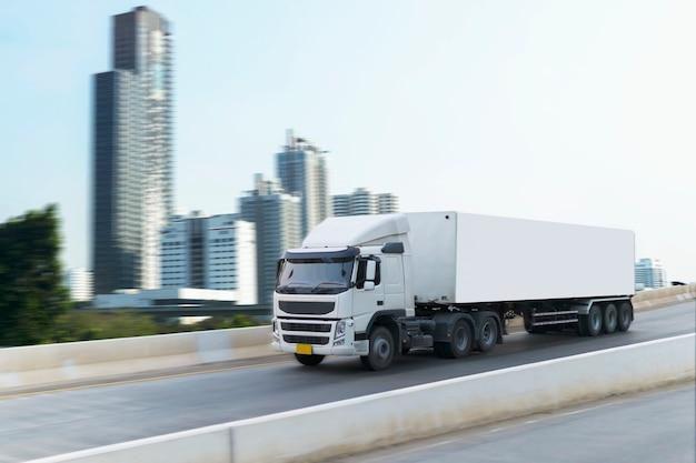 Biała ciężarówka na drogowym kontenerze na autostradzie, importuje, eksportuje logistyczny transport na trasie ekspresowej