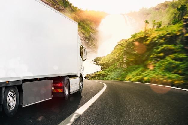 Biała ciężarówka poruszająca się po drodze w naturalnym krajobrazie o zachodzie słońca