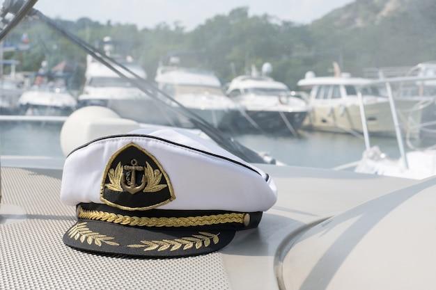 Biała czapka kapitana morza na desce rozdzielczej łodzi, łodzie są zaparkowane