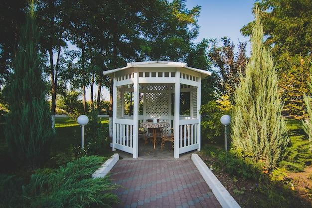 Biała drewniana altana na ulicy w zielonym parku. przytulne miejsce do spędzania czasu