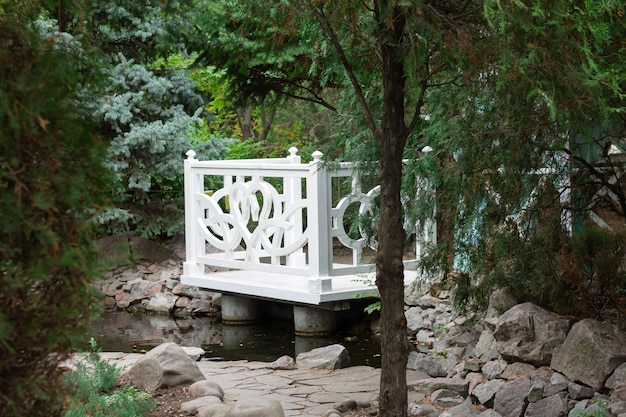 Biała drewniana altana w letnim zielonym parku. przytulna alkowa ogrodowa do spędzania czasu na łonie natury