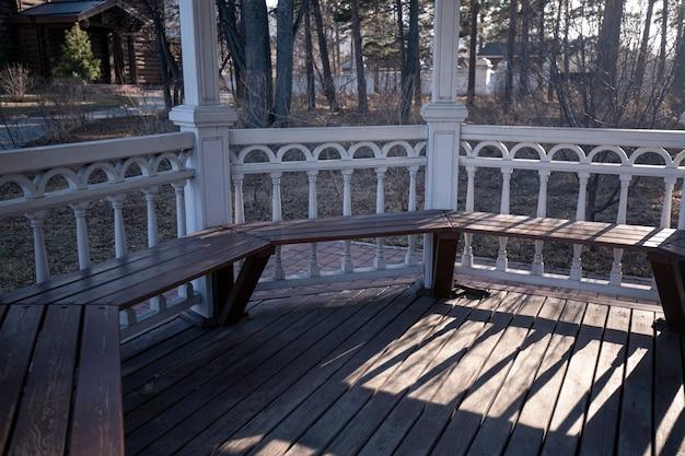 Biała drewniana altana w parku wczesną wiosną