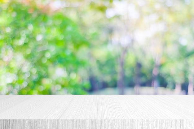 Biała drewniana półka i rozmycie zielone drzewo natura