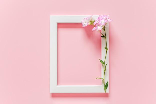 Biała drewniana ramka na zdjęcia i kwiaty na różowo z copyspace
