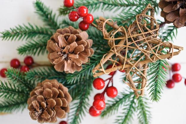 Biała drewniana tekstura z liściem sosny, rożkami sosnowymi lub iglastymi, czerwonymi kulkami holly i drewnianą gwiazdą w koncepcji bożego narodzenia. drewniany deski tło w odgórnego widoku mieszkaniu kłaść z kopii przestrzenią dla bożenarodzeniowej tapety.
