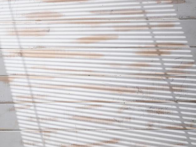 Biała drewniana tekstura ze światłem z okna przez rolety