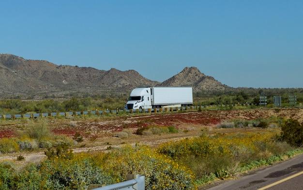 Biała, duża platforma, amerykańska, długodystansowa, półciężarówka, poruszająca się po szerokiej, podzielonej zakrętach z górami