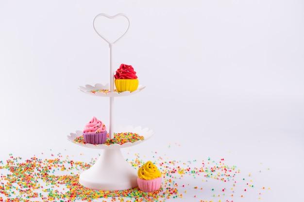 Biała dwupoziomowa taca i miniaturowe wielobarwne babeczki cukrowe z posypką