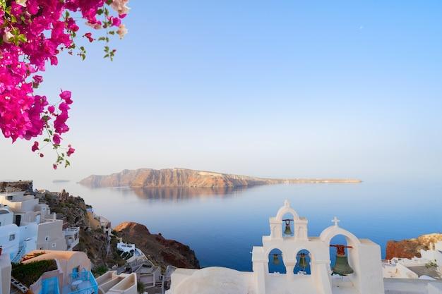 Biała dzwonnica kościoła nad morzem i kalderą, wyspa santorini z kwiatami