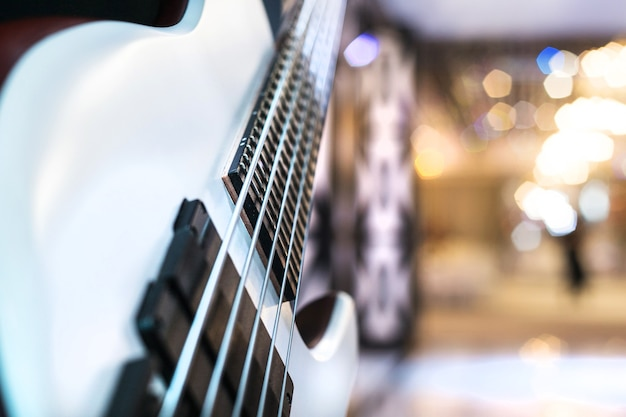 Biała elektryczna gitara basowa z bliska pięć strun. niewyraźne tło.