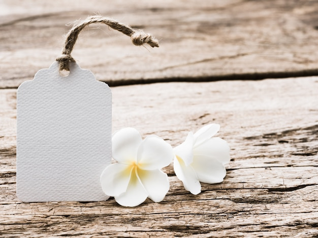 Biała etykieta papierowa ozdobiona kwiatami plumeria na rustykalnym drewnianym stole