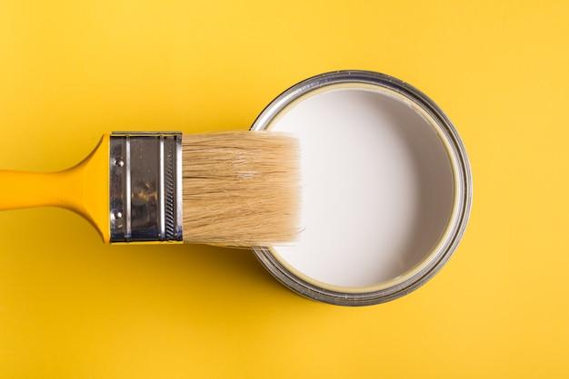 Biała farba może z widokiem z góry pędzla na żółtym tle