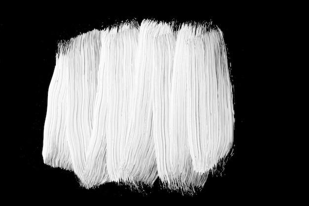 Biała farba olejna na czarnym tle, pociągnięcia pędzlem farby, tekstury