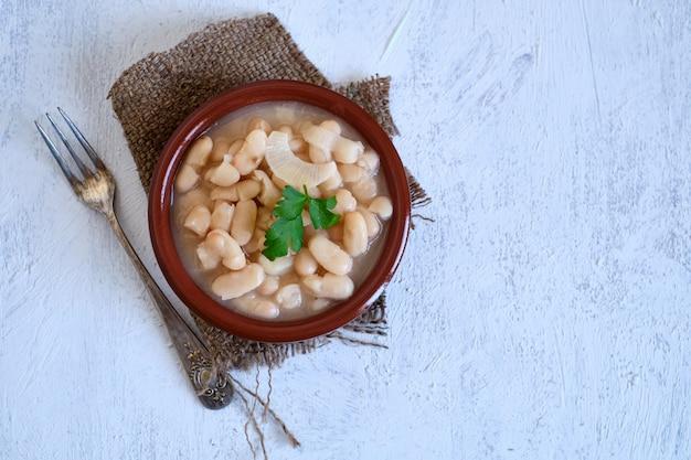 Biała fasola gotowana tylko z cebulą w glinianym garnku. czysta i zdrowa żywność