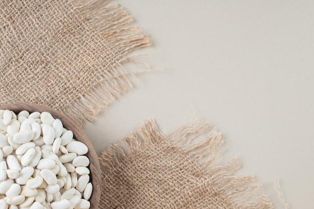 Biała fasola w tackach na żywność na betonie.