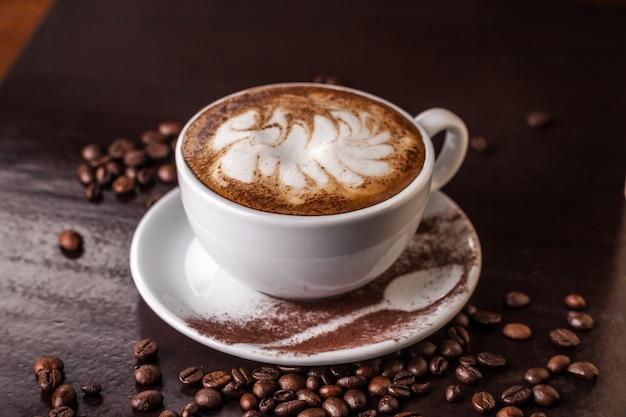 Biała filiżanka cappuccino na starym drewnianym stole, ziarna kawy rozrzucone na stole