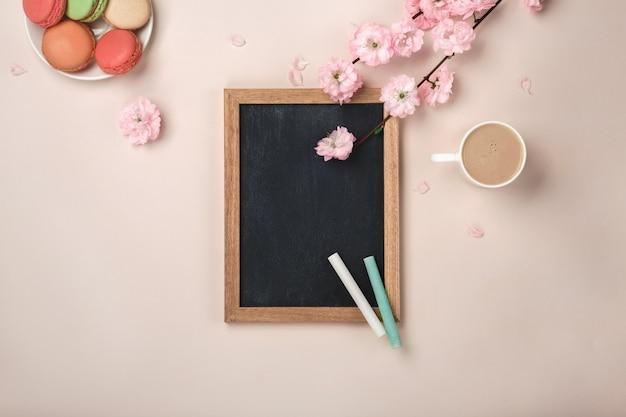 Biała filiżanka cappuccino z sakura kwiatami, macarons, kredowa deska na pastelowym różowym tle