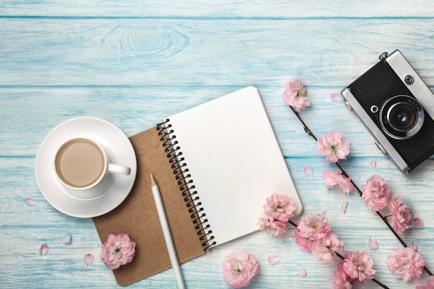 Biała filiżanka cappuccino z sakura kwiatami, notatnikiem i starą fotografii kamerą na błękitnym drewnianym stole