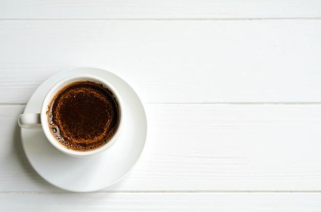 Biała filiżanka czarna kawa na bielu malował drewnianego tło