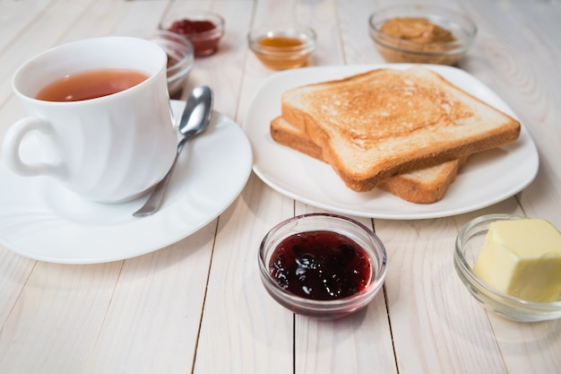 Biała filiżanka czarnej herbaty z kanapkami lub grzankami z masłem orzechowym, pastą czekoladową i galaretką truskawkową, porzeczkową i morelową lub dżemem na białym drewnianym stole, z bliska, koncepcja śniadanie
