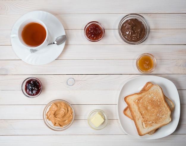 Biała filiżanka czarnej herbaty z kanapkami lub grzankami z masłem orzechowym, pastą czekoladową i galaretką z truskawek, porzeczek i moreli lub dżemem na białym drewnianym stole, widok z góry, układ płaski, koncepcja śniadania