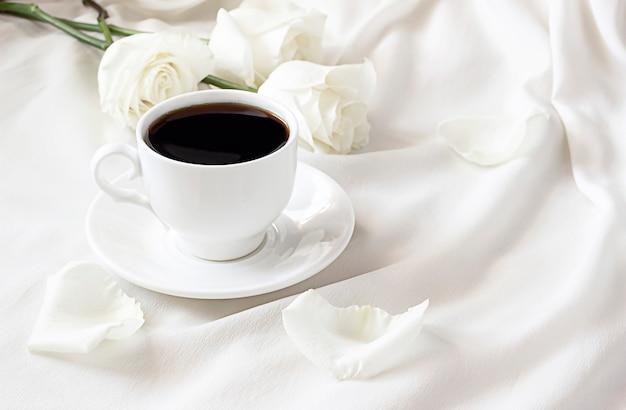 Biała filiżanka czarnej kawy na białym łóżku w pobliżu białych róż