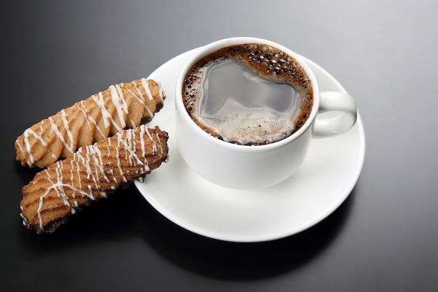 Biała filiżanka czarnej kawy z ciastkami na ciemnej powierzchni