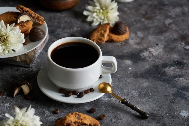 Biała filiżanka czarnej mocnej kawy z ziaren kawy i ciastek
