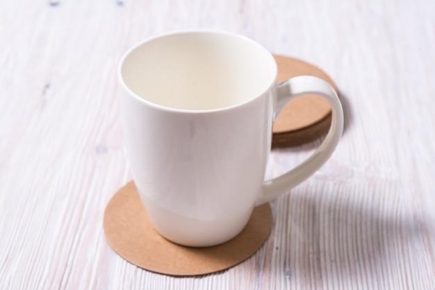 Biała filiżanka do herbaty z potvelain na tekturowych okrągłych podstawkach, podkładka na kubek, mata, uchwyt