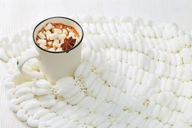 Biała filiżanka gorącej czekolady z marshmallows na białej pomponowej przędzy.