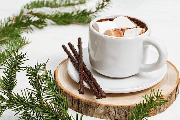 Biała filiżanka gorącej czekolady z marshmallows ozdobiona jodłowymi gałązkami