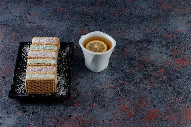 Biała filiżanka gorącej herbaty z czarnym talerzem słodkich gofrów na ciemnym