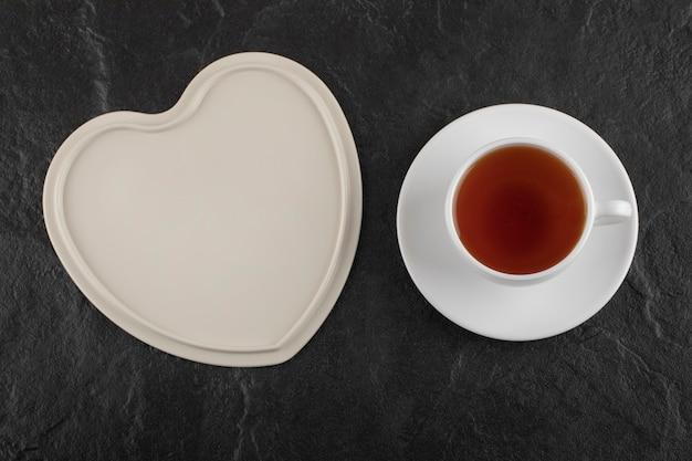Biała filiżanka gorącej herbaty z pustym talerzem.