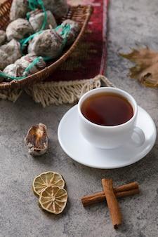 Biała filiżanka gorącej herbaty z suszonymi owocami postawiona na kamiennym stole.