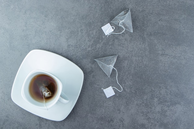 Biała filiżanka gorącej herbaty z torebkami.