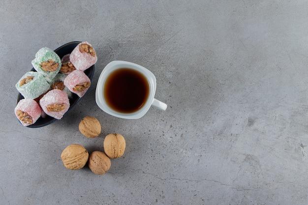 Biała filiżanka gorącej herbaty z tradycyjnymi tureckimi przysmakami i zdrowymi orzechami włoskimi