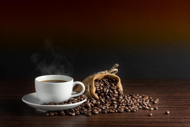 Biała filiżanka gorącej kawy z dymem z ziaren kawy i wory pełne ziaren kawy z liną