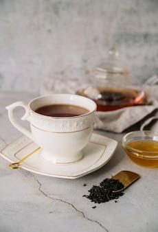 Biała filiżanka herbaty na marmurowym tle