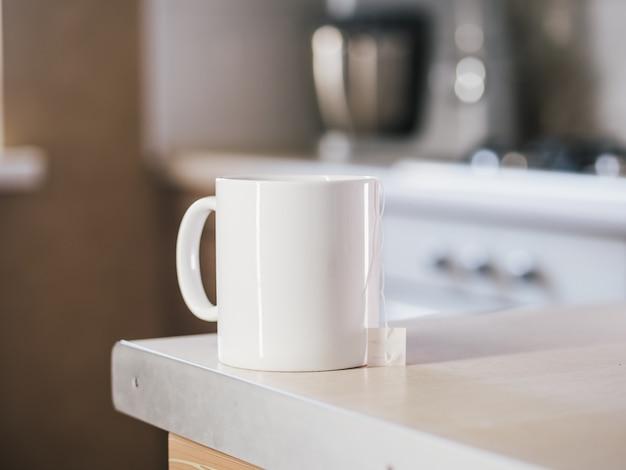 Biała filiżanka herbaty w kuchennym stole