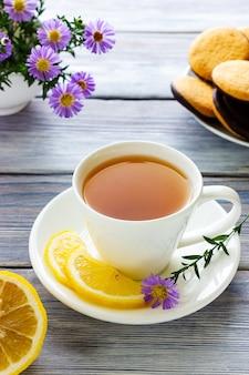 Biała filiżanka herbaty z bajglem cytrynowym i ciasteczkami przerwa na lunch w kawiarni