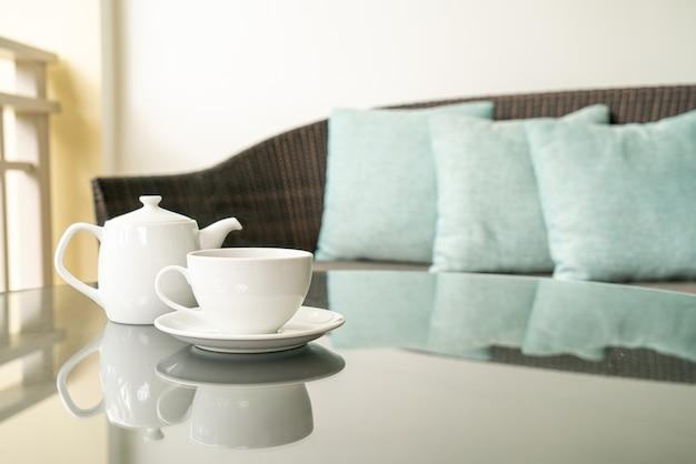 Biała filiżanka herbaty z czajniczkiem na stole