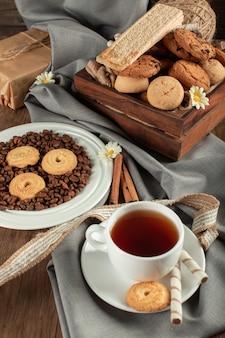 Biała filiżanka herbaty z owsianymi ciastkami i herbatnikami