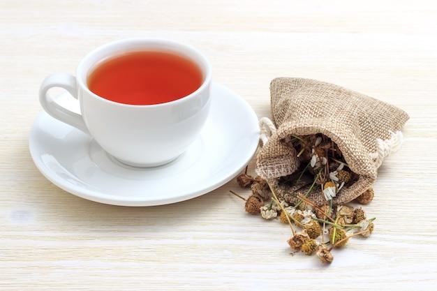 Biała filiżanka herbaty z rumiankiem w etui na białym tle drewnianych