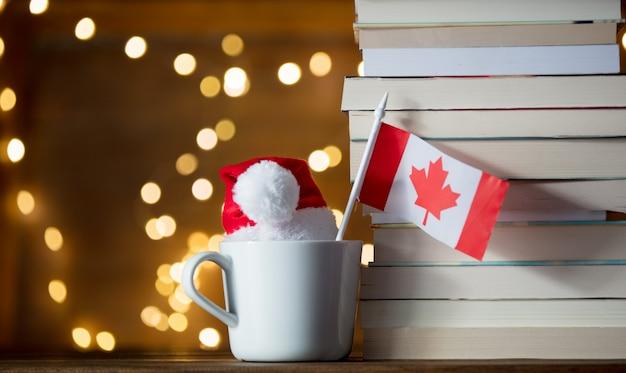 Biała filiżanka i bożenarodzeniowy kapelusz z polska flaga blisko książek