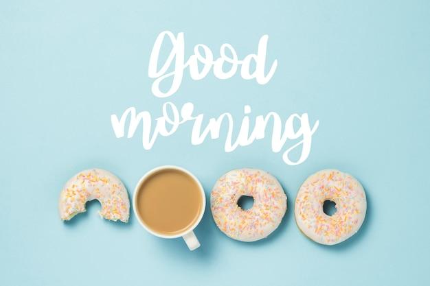 Biała filiżanka, kawa lub herbata z mlekiem i świeżymi smacznymi pączkami na niebiesko. dodano tekst dzień dobry. koncepcja piekarni, świeże wypieki, pyszne śniadanie, fast food. leżał płasko, widok z góry.