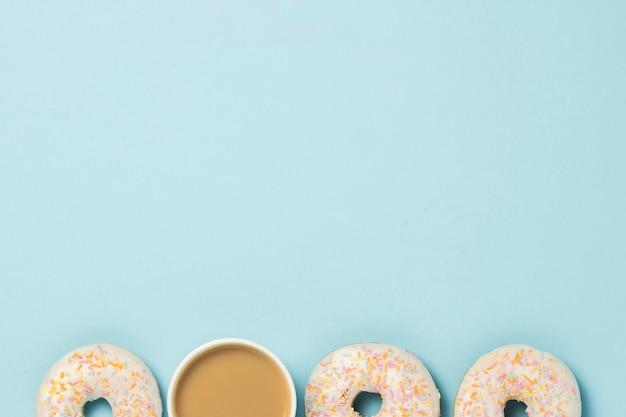 Biała filiżanka, kawa lub herbata z mlekiem i świeżymi smacznymi pączkami na niebiesko. koncepcja piekarni, świeże wypieki, pyszne śniadanie, fast food. leżał płasko, widok z góry.