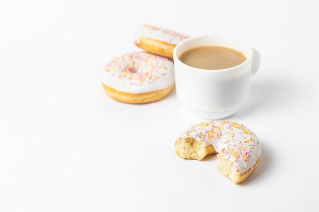 Biała filiżanka, kawa lub herbata z mlekiem i świeżymi smakowitymi pączkami, słodki stubarwny dekoracyjny cukierek na białym tle. koncepcja piekarni, świeże wypieki, pyszne śniadanie, fast food.